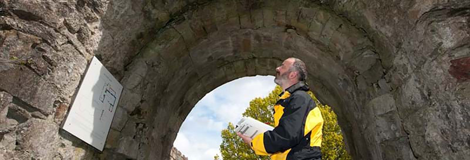 Man holding paperwork and looking at a plan on the wall of a historic archway. banner image