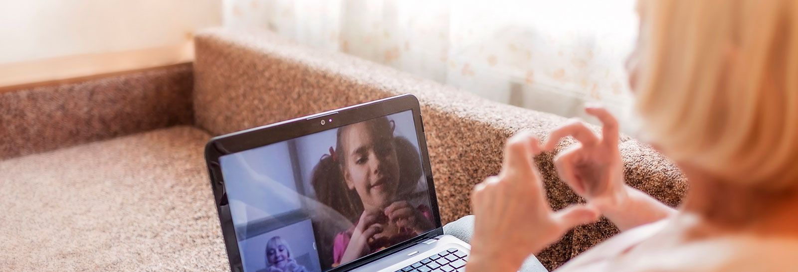 Older woman and grandchild in video call banner image
