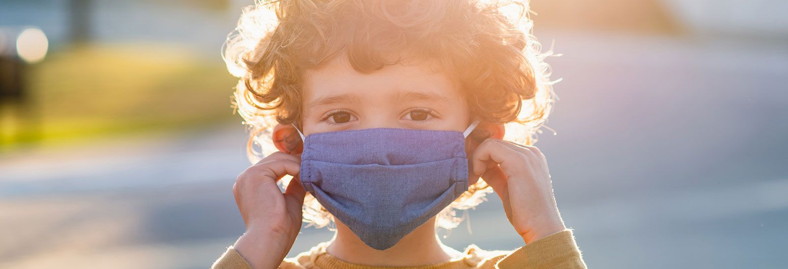 Young child wearing a face mask banner image